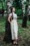 Muchacha en sarafan ruso tradicional del vestido inclinada contra abedul Foto de archivo libre de regalías