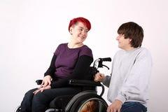 Muchacha en silla de ruedas que habla con el ayudante Imagen de archivo libre de regalías