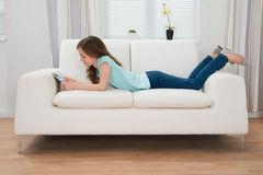 Muchacha en Sofa Looking At Digital Tablet Fotos de archivo libres de regalías