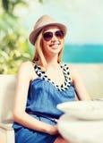 Muchacha en sombras en café en la playa Foto de archivo