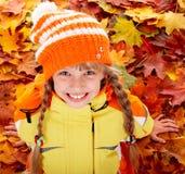 Muchacha en sombrero anaranjado del otoño en fondo de la hoja. Fotografía de archivo