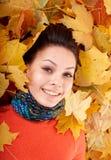Muchacha en sombrero anaranjado del otoño en grupo de la hoja. Fotos de archivo libres de regalías