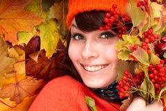 Muchacha en sombrero anaranjado del otoño en grupo de la hoja. Imagen de archivo