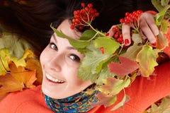 Muchacha en sombrero anaranjado del otoño en grupo de la hoja. Imagen de archivo libre de regalías