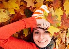 Muchacha en sombrero anaranjado del otoño en grupo de la hoja. Foto de archivo