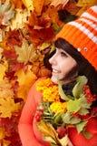 Muchacha en sombrero anaranjado del otoño, grupo de la hoja, flor. Fotos de archivo