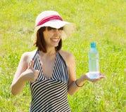 Muchacha en sombrero con la botella Foto de archivo libre de regalías