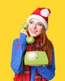 Muchacha en sombrero de la Navidad con el teléfono Fotografía de archivo libre de regalías