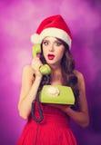Muchacha en sombrero de la Navidad con el teléfono verde Imagenes de archivo