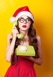 Muchacha en sombrero de la Navidad con el teléfono verde Foto de archivo libre de regalías