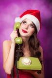 Muchacha en sombrero de la Navidad con el teléfono verde Fotografía de archivo