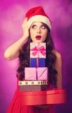 Muchacha en sombrero de la Navidad con los regalos Fotografía de archivo libre de regalías