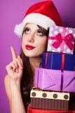 Muchacha en sombrero de la Navidad con los regalos Fotografía de archivo