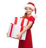 Muchacha en sombrero del ayudante de santa con muchas cajas de regalo Imagen de archivo