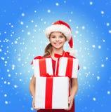 Muchacha en sombrero del ayudante de santa con muchas cajas de regalo Foto de archivo libre de regalías