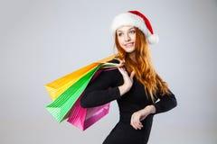 Muchacha en sombrero del invierno con los panieres sobre gris imágenes de archivo libres de regalías