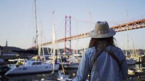 Muchacha en sombrero en el terrapl?n cerca del 25to aplril del puente en Lisboa almacen de metraje de vídeo