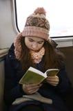 Muchacha en sombrero hecho punto y adentro tren leído manoplas Fotos de archivo