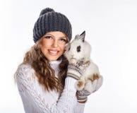 Muchacha en sombrero hecho punto y el suéter que sostienen el conejo Imágenes de archivo libres de regalías