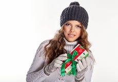 Muchacha en sombrero hecho punto y el suéter que sostienen los regalos Imagen de archivo