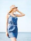 Muchacha en sombrero que camina en la playa Fotografía de archivo