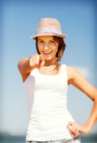 Muchacha en sombrero que señala en usted en la playa Imágenes de archivo libres de regalías
