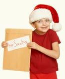 Muchacha en sombrero rojo con la letra a santa - el concepto de la Navidad de las vacaciones de invierno, amarillea entonado Fotos de archivo
