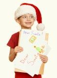 Muchacha en sombrero rojo con la letra a santa - el concepto de la Navidad de las vacaciones de invierno, amarillea entonado Fotografía de archivo libre de regalías