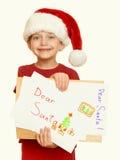 Muchacha en sombrero rojo con la letra a santa - el concepto de la Navidad de las vacaciones de invierno, amarillea entonado Foto de archivo
