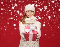 Muchacha en sombrero, silenciador y guantes con la caja de regalo Fotografía de archivo libre de regalías