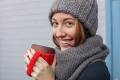 Muchacha en sombrero y bufanda del invierno que bebe la bebida caliente para mantener caliente Fotos de archivo