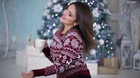 Muchacha en suéter brillante delante del abeto almacen de metraje de vídeo