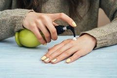 Muchacha en suéter marrón con la manicura amarilla que aplica la crema de la mano, Imagen de archivo