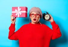Muchacha en suéter rojo con la caja de regalo y el despertador foto de archivo