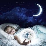 Muchacha en su cama y globo que brilla intensamente Foto de archivo