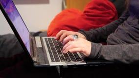 Muchacha en su ordenador portátil en dormitorio metrajes