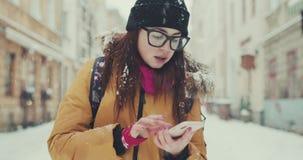 Muchacha en su 20s usando el smartphone para las direcciones Turista perdido que usa el app en el teléfono móvil, textos vía su t almacen de video
