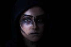 Muchacha en sudadera con capucha con maquillaje asustadizo de la cara en fondo negro Fotos de archivo