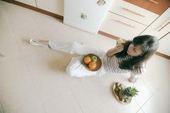 Muchacha en suelo que come la fruta fotografía de archivo
