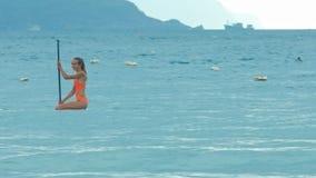 Muchacha en tablero de paletas del bikini en las rodillas que pasan la costa montañosa metrajes