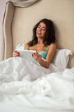 Muchacha en tableta de la tenencia de la cama foto de archivo libre de regalías