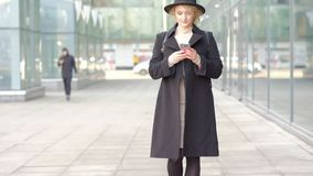 Muchacha en textos negros en el teléfono que camina a lo largo de la pared de la ventana de cristal almacen de metraje de vídeo