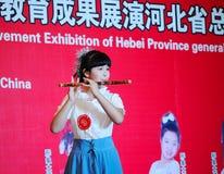 Muchacha en tocar la flauta de bambú Foto de archivo