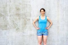 Muchacha en top sin mangas azul y pantalones cortos sobre la sonrisa de la pared Fotografía de archivo libre de regalías