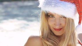 Muchacha en traje de baño y el sombrero rojos de santa que liga y que presenta en la playa lentamente almacen de video