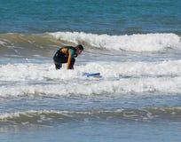Muchacha en traje de la prenda impermeable del color que ejercita en practicar surf a bordo Fotos de archivo libres de regalías