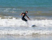 Muchacha en traje de la prenda impermeable del color que ejercita en practicar surf a bordo Imágenes de archivo libres de regalías