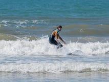 Muchacha en traje de la prenda impermeable del color que ejercita en practicar surf a bordo Foto de archivo