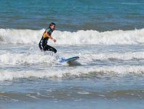 Muchacha en traje de la prenda impermeable del color que ejercita en practicar surf a bordo Foto de archivo libre de regalías