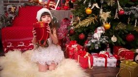 Muchacha en traje del ` s del Año Nuevo cerca del árbol de navidad con la sorpresa del ` s del Año Nuevo, vacaciones de la feliz  almacen de video